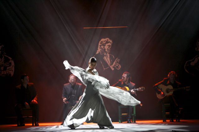 Sara Baras in Voces; Photo: Santana de Yepes. Baras' white scarf cascades around her as she dances flamenco with musicians in the background.