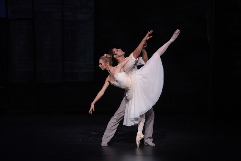 A dancer in white poses in a penchee en pointe while her partner stands behind her.