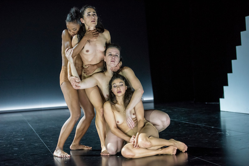 Four bare breasted women stand and sit in a cascading line.
