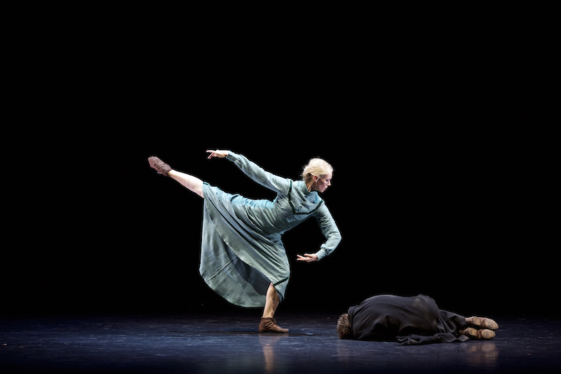 A woman in a long green dress plies on one leg peering over a man crumpled on the floor. Her other leg extends high in the air.