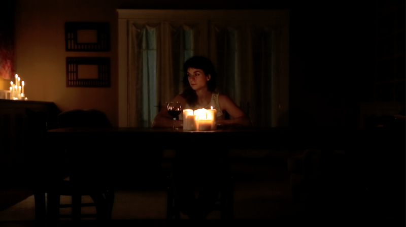 Molly Lieber who plays Jeanine stands behind a piano. A glass of red wine sits besides her. The room is dimly lit by candelight.