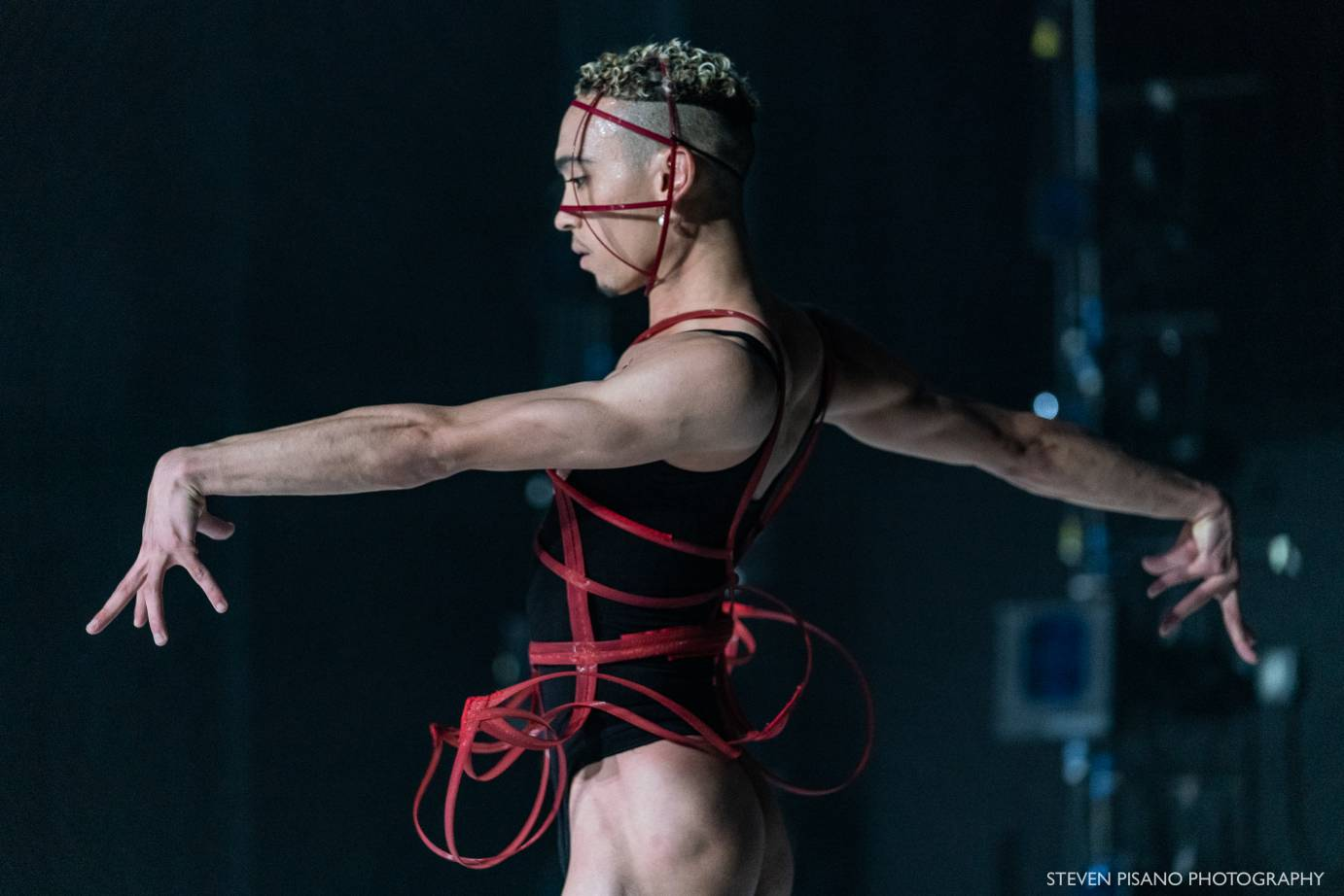 A dancer in a black leotard and red ribbon outstretches their arm their wrists bent.