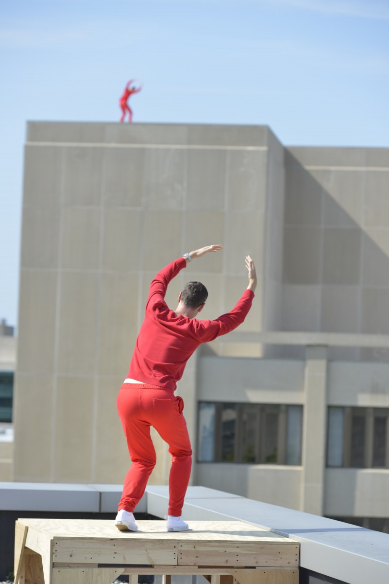 A man on a building in the distance in red. Another man in all red stands on a nearby perch with his back facing the camera.