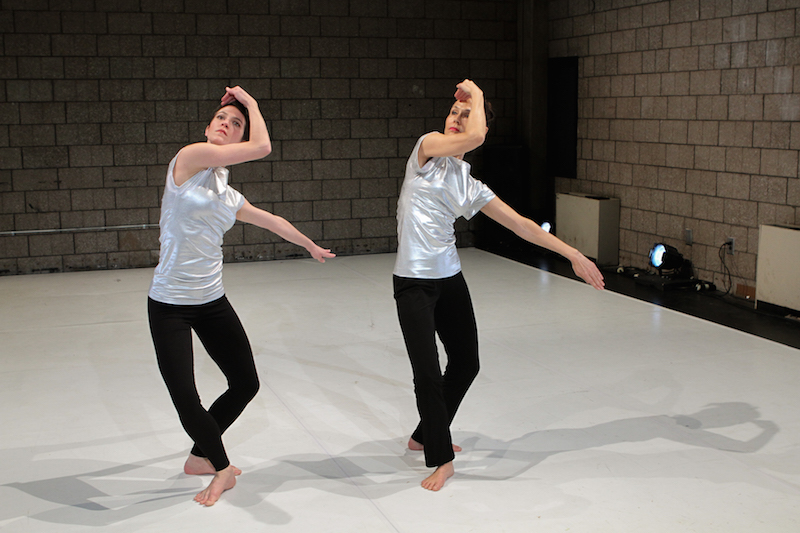 Hands frame the dancers' faces while their legs are in a plie
