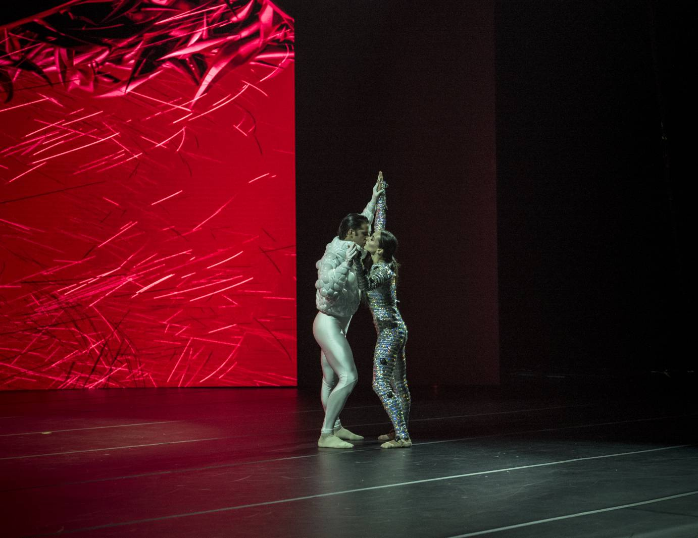 Two dancers against a red projection