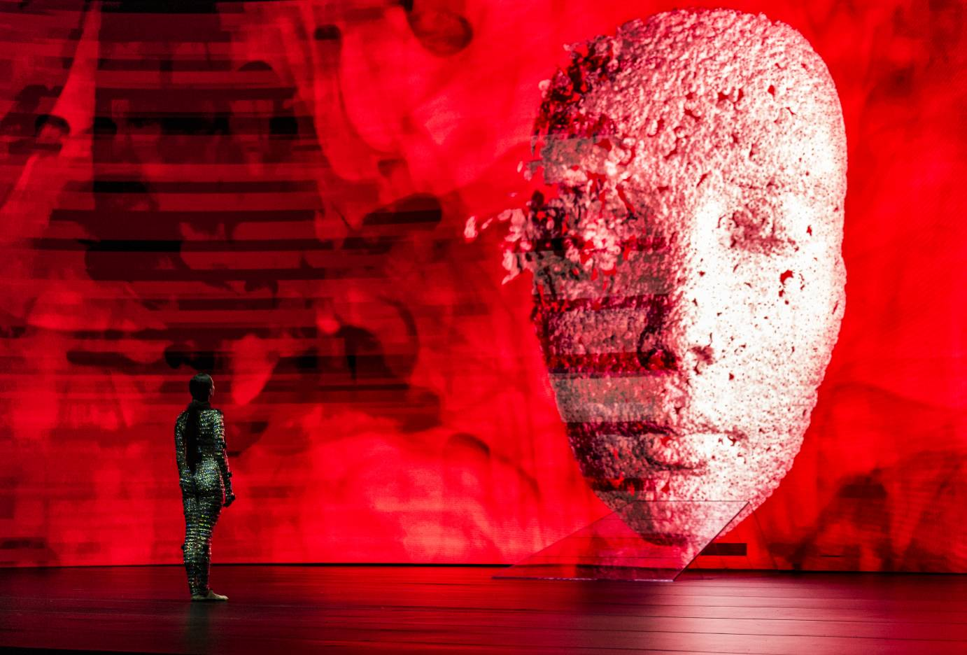 Female dancer stares at mask projected on red background