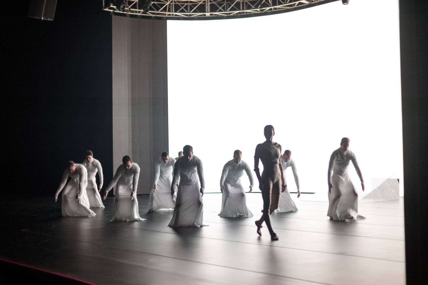 One female dancer in front of eight men in white
