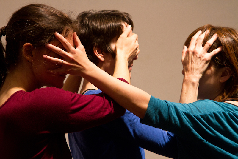 Three women in bright colored shirts place their hands over one another's faces