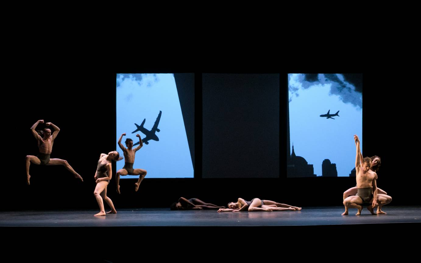 Dancers form a dynamic stage-scape in front of an image of planes in New York