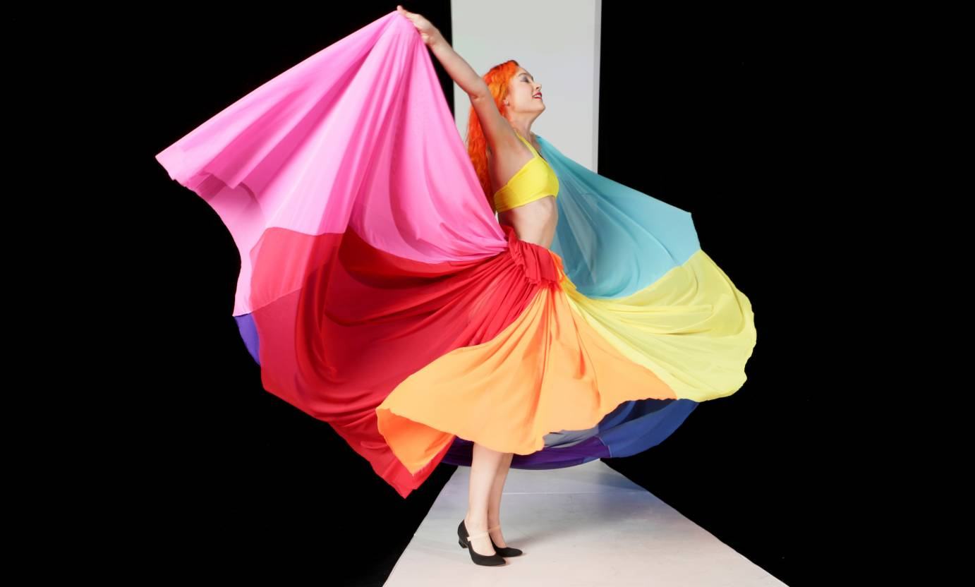 A woman with orange hair lifts a rainbow colored skirt off to her sides.