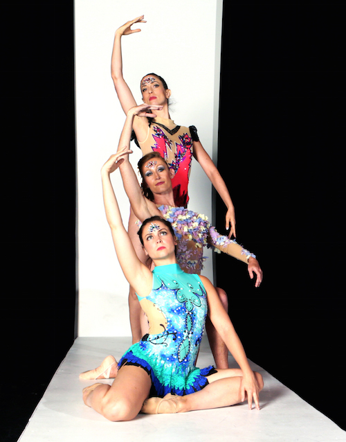 Three dancers stand and sit in a cascading line. They each wear beweled leotards.