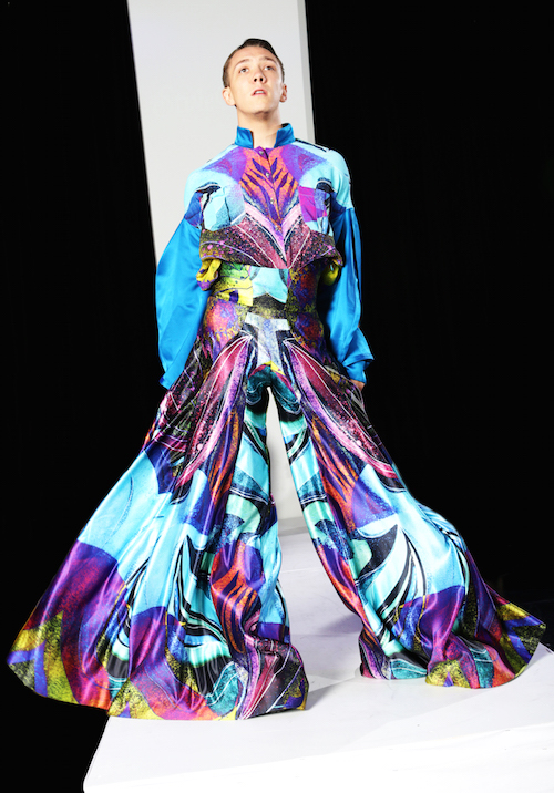 A dancer in a multicolor gown. The gown includes bright purple, shades of blue and neon yellow. The skirt swishes as they walk.