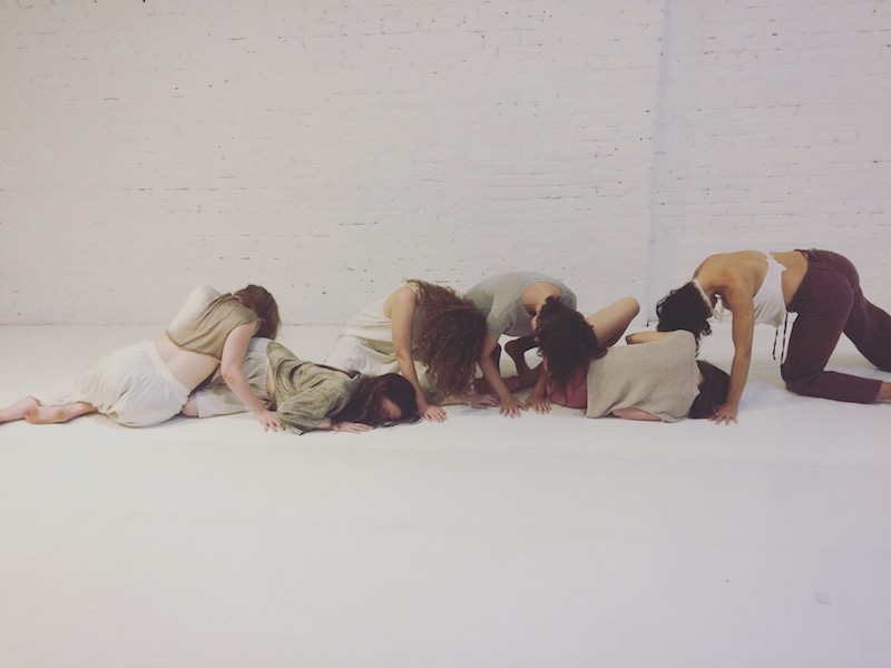 A group of artists in a long tableau arrange themselves on the floor.