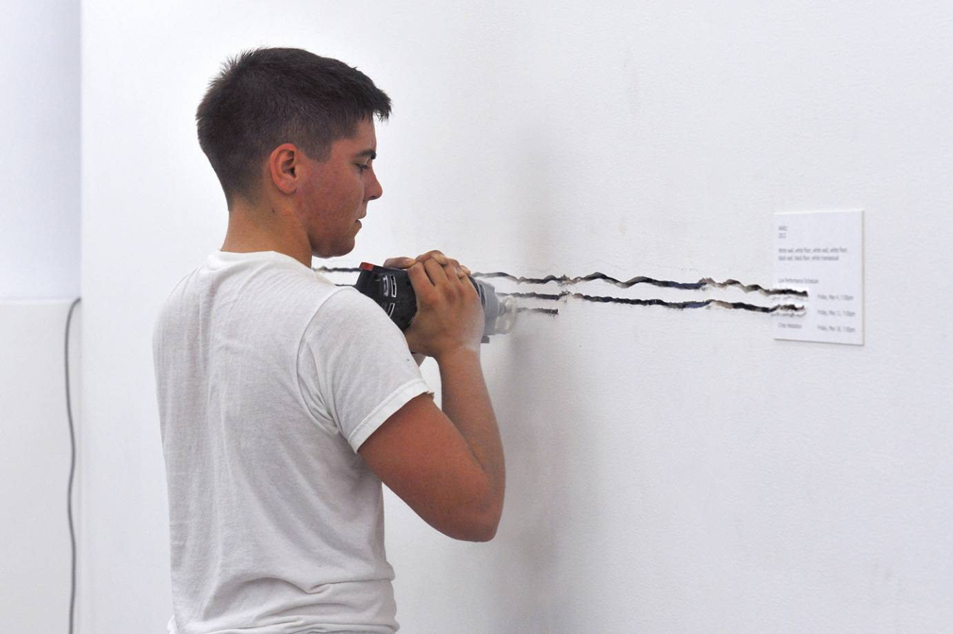 Yve Laris Cohen, dressed in a white t-shirt, creating deep lines in a white wall using a power tool.