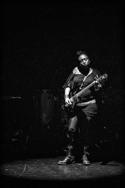 A black and white photo of Tamar Kali. She wears a long off-the-shoulder sweater and tights. She closes her eyes as she plays her guitar onstage.