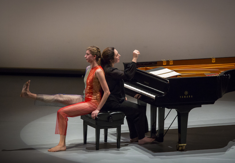 Dinnerstein and Jones sit back to back on the piano bench. Dinnerstein lifts her hand off the piano as if she just finished playing the last note of the variation. Jones flexes her right foot and lifts her leg parallel to the ground.