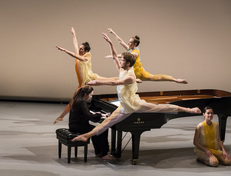 Three dancers in colorful gauzy tunics leap into the air around a piano. A pianist intently plays on. Another dancers kneels in front of the piano and looks out to the audience.