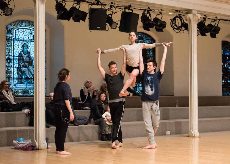 Pam Tanowitz directs her dancers as two men lift a female in an overhead position