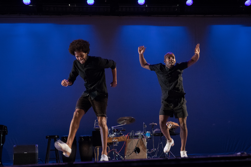 Two men in black button ups and shorts and white taps dance in