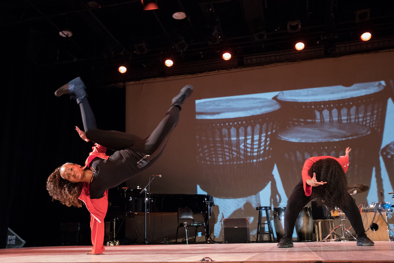 A b-girl lifts her body off the ground with one hand. Her legs are bent and above her head. Another dancer bends her torso over her legs which are in a deep squat.