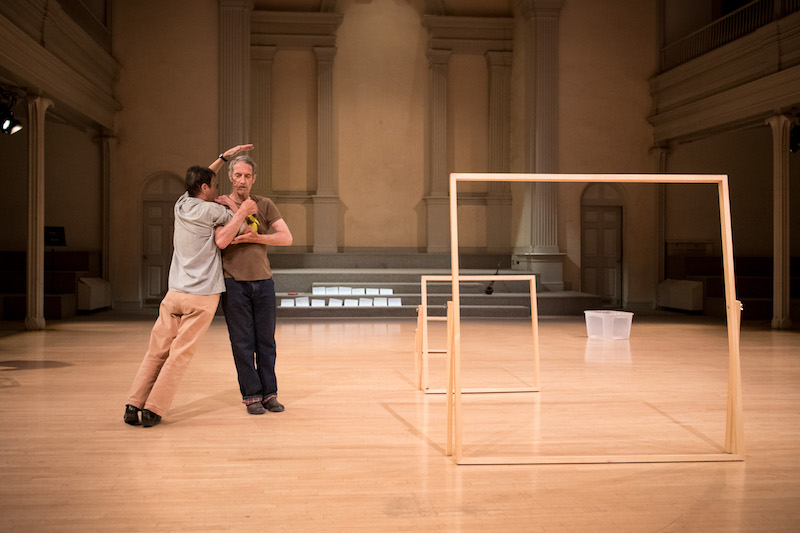 Steve Paxton stands erect as Yvonne Rainer leans against him. To their left, are three wooden picture frames of varying heights.