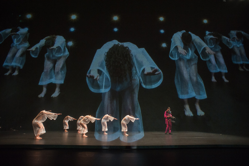 dancers in filmy white jumpsuits stand in side profile from the audience with their arms outstretched alongside their faces. A man in a red suit operates a steadicam to the right of them. They are projected larger-than-life on the scrim behind them.