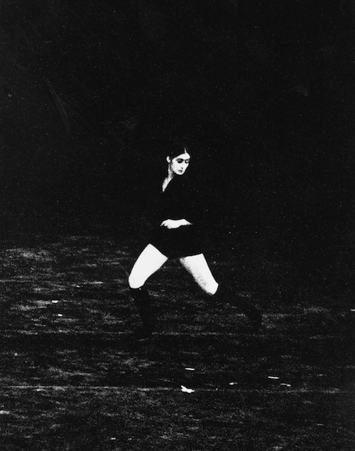 An archival photo of Twyla Tharp dancing in The Fugue in 1971. The photo is black and white and grainy. Tharp wears shorts and knee high boots