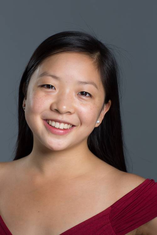 A headshot of dancer Kara Chan who has long black hair and wears a magenta off the shoulder top