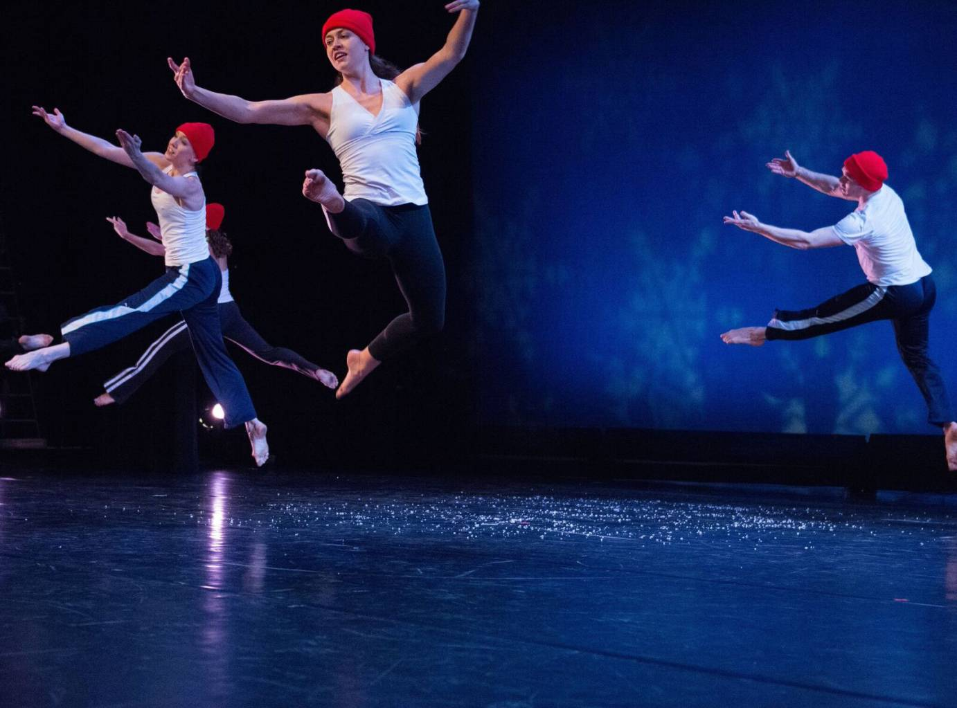 Dancers in red beanies leap