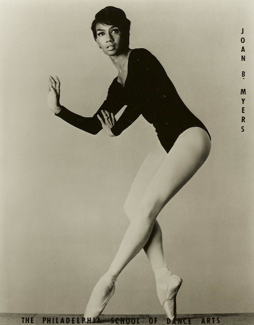 A photo of a young Joan Myers Brown. She wears a black leotard, light tights and pointe shoes. She pose en pointe with her arms bent in front of her torso. She looks towards the camera.