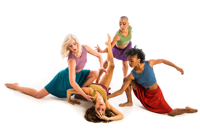 Four women in colorful tanks and skirt spiral and lunge to the ground. One woman lays on her back.