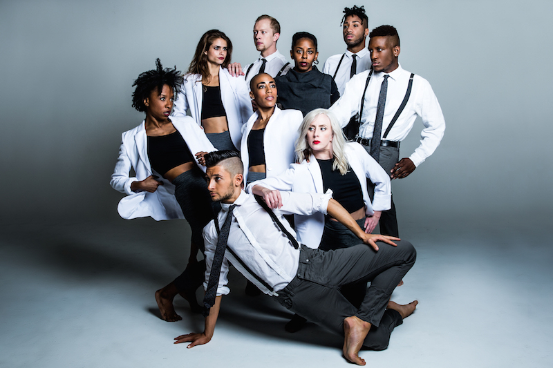 Dancers of Elisa Monte Dance wear black and white basics (blazers, jeans, button ups) and pose in a clump. Their gazes are in different directions.