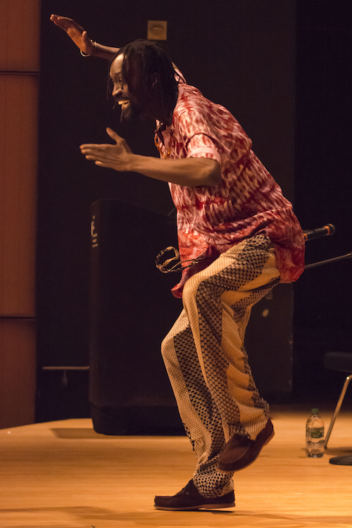 Maguette Camara, with a wide grins, performs with one leg hovering off the ground and one hand above his head