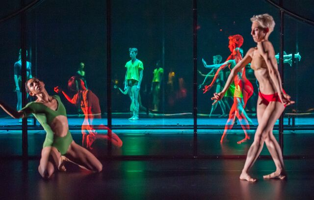 Two dancers in florescent leotards and trunks are reflected in the mirror set, multiplying their image countless times
