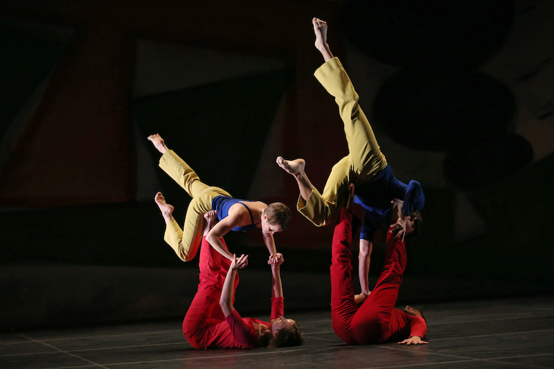 Two dancers in red on the floor hold up their respective partners by their feet and hands. It looks like their partners are floating on the stomachs in the air
