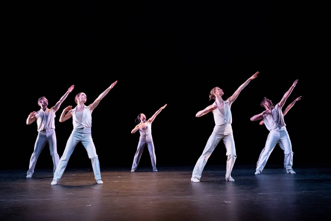 A group of dancers in white pants in tops stand in a wide stance. Their left arm is placed on a high diagonal while their right arm is bent at the elbow.