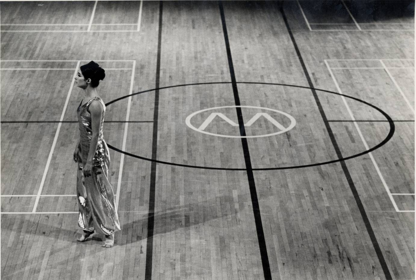 A woman stands in relve in side profile on basketball court. She's barefoot and wears an iridescent costume.