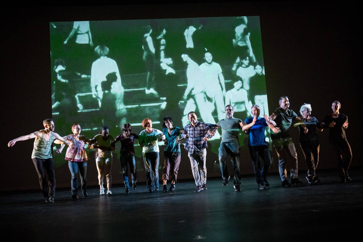 A grainy archival video of Twyla Tharp dancers is projected on stage. In front of it, a group of dancers and volunteers stand in a straight line with their arms linked.