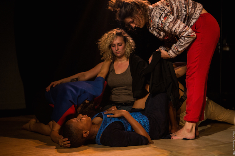 Jennifer Harge lays on her back while another dancer curls up next to her. Her face is hidden. Nadia Tykulsker knees besides them while EmmaGrace Skove Epps stands over them.