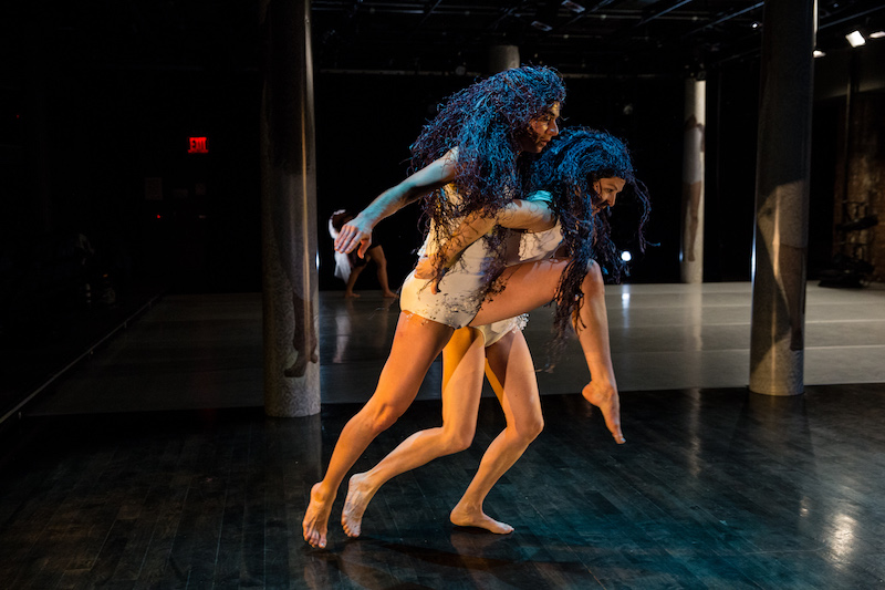 Olson and Lieber in short white unitards and navy raffia wigs. Olson holds Lieber by the waist as Lieber lunges forward.