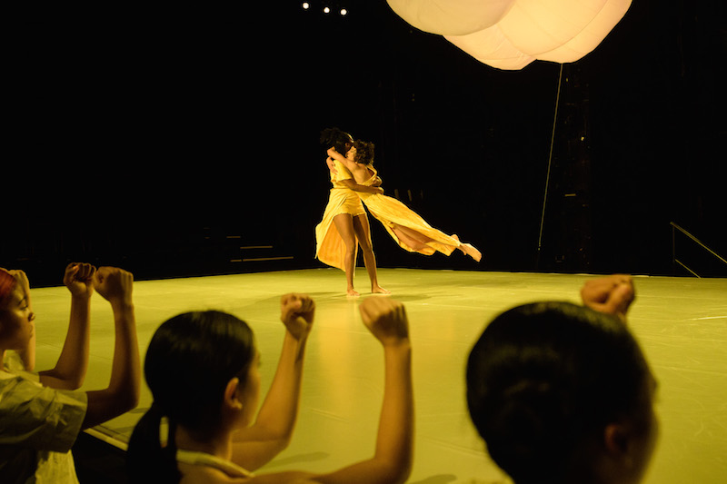 A dancer in marigold holds another artist and spins her around. A illuminated large lantern floats above them