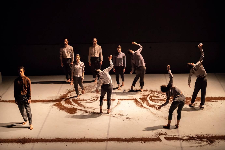 Nine dancers stand among furrows of dirt