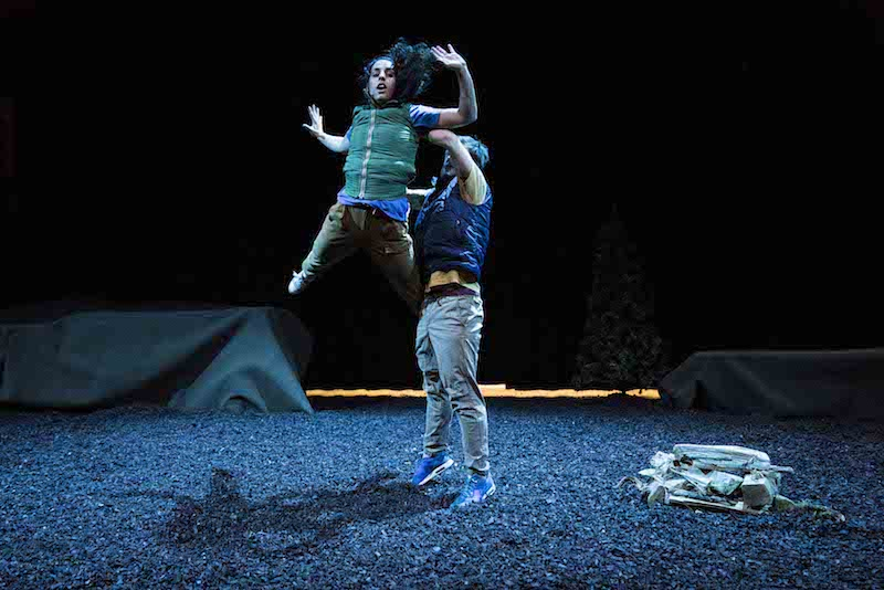 A woman in a green outdoor vest and cargo pants is in mid air after a male dancer throws her. A tent is in the background. Peet and dirt cover the stage floor.