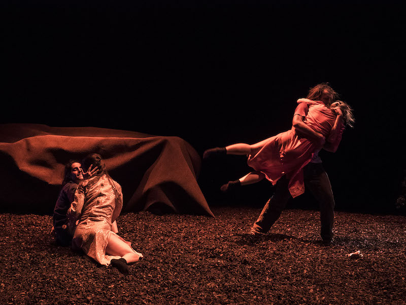 One couple sits on the peet-covered floor. One dancer touches their hand to the other's cheek. Another couple embrace one another. The women's legs swing in the air. A tent-looking shelter is in the background.