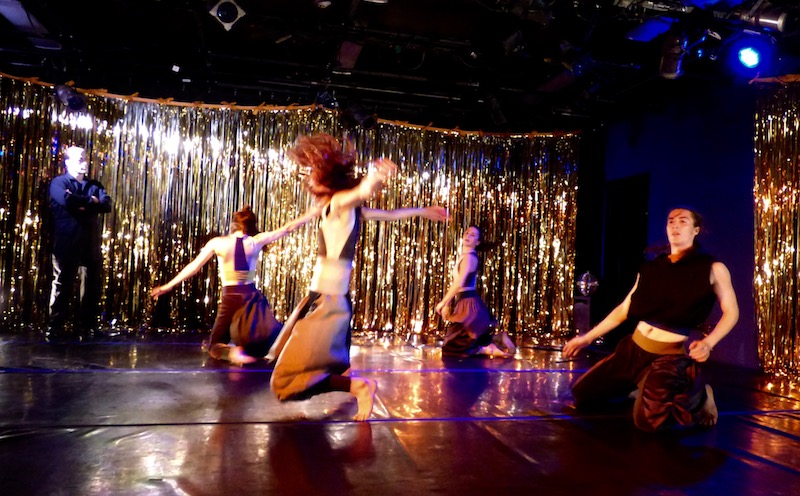A group of dancers kneel on stage. Around the perimeter of the room are gold streamers. A man with his arms crossed stands and watches them.
