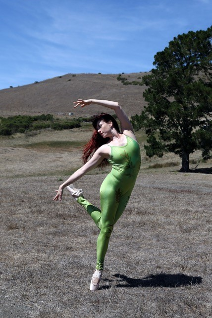 A red-haired woman dances on a grassy field en pointe