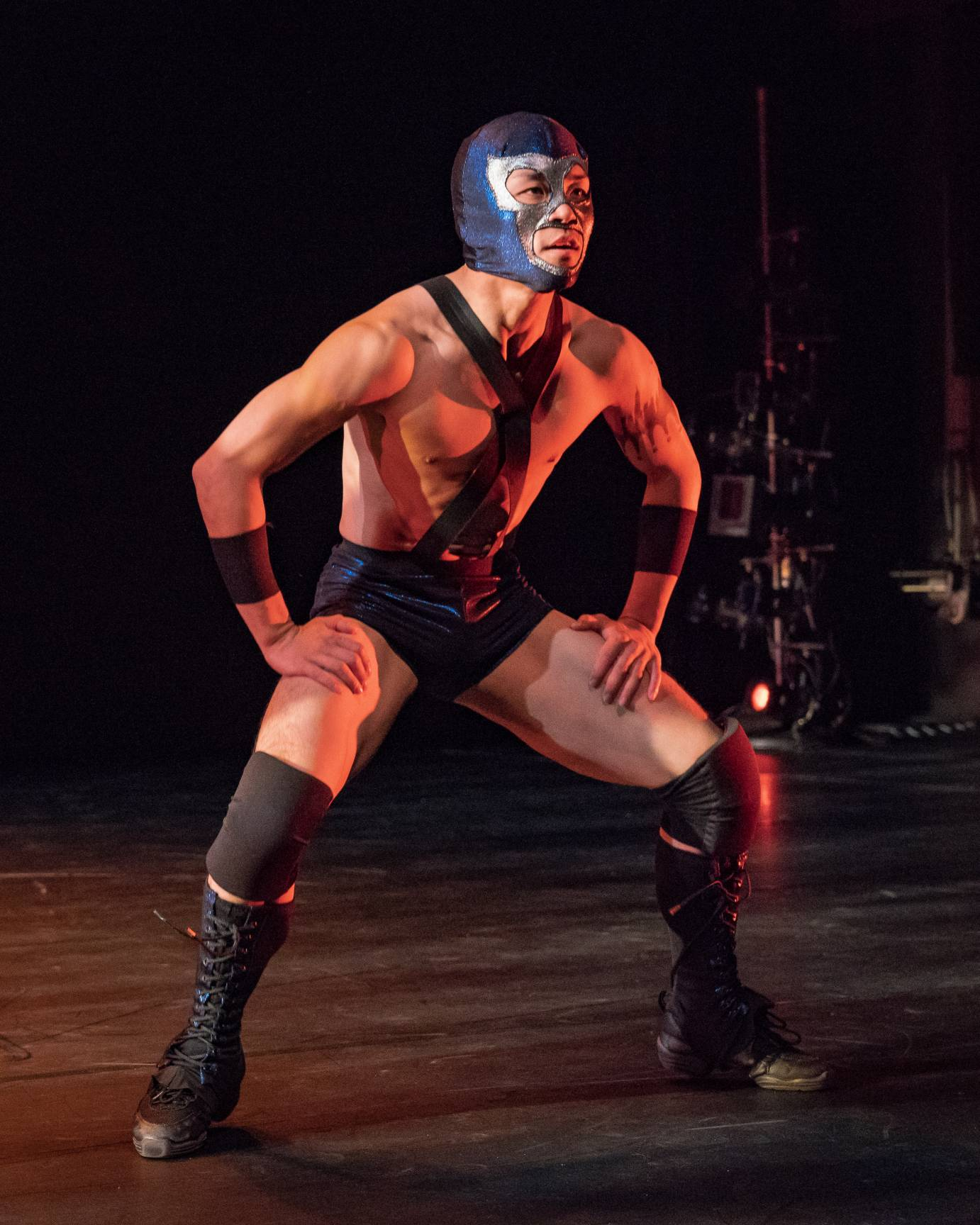A man in a wrestling mask assumes a squat position looking out to the audience