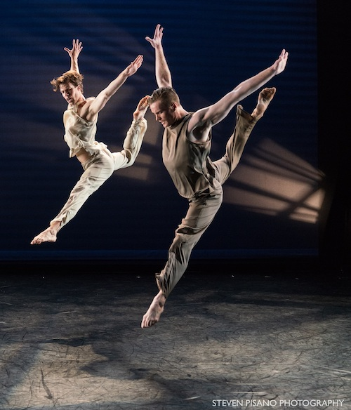 Two dancers leap into the air. One leg bends behind them while other extends in front. Their arms are above their head.