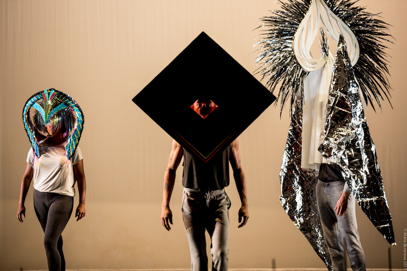 Three dancers face the audience wearing elaborate masks. Some have fringy paper, are shiny, are geometric and one is very tall.