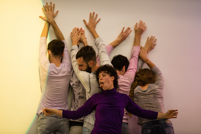 A group of dancers in a clump against the wall. One woman in a purple turtleneck sticks her tongue out.